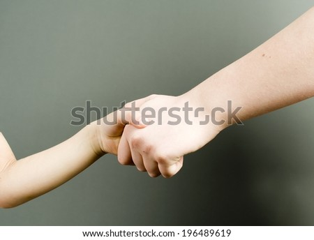 An adult and a child holding hands with each other.