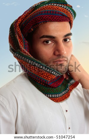 An adult arab middle eastern man dressed in traditional clothing.  He has a keffiyeh turban on his head. - stock photo