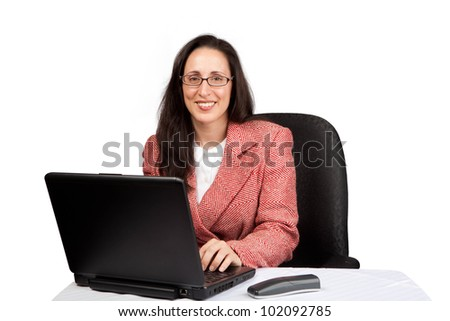 An adult businesswoman wearing a suite on a isolated white background working on a laptop with a phone on her desk - stock photo