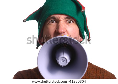 An adult Christmas elf is yelling into a megaphone and facing the camera - stock photo