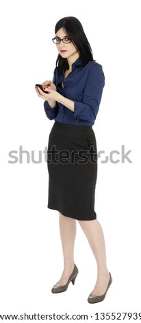 An adult (early 30's) black haired caucasian woman, wearing a blue buttoned shirt and a dark gray skirt using a cellular phone. Isolated on white background. - stock photo