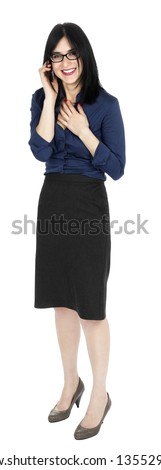An adult (early 30's) black haired caucasian woman, wearing a blue buttoned shirt and a dark gray skirt; looking at the camera while laughing on the phone. Isolated on white background. - stock photo