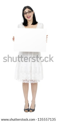 An adult (early 30's) woman, wearing a lovely white summer dress and holding a blank sign in her front while giving the camera what seems to be a loud cheer (Surprise!!!). Isolated on white background - stock photo