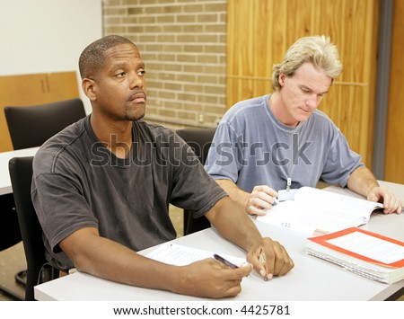 An adult education student in school with a bored expression. - stock photo