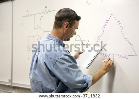 An adult education teacher drawing an electrical diagram on the board. - stock photo
