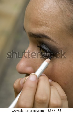 An adult female model gets eyeliner applied to her - stock photo