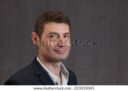 An adult male in his early forties wearing a jacket and shirt.  He is smiling. - stock photo