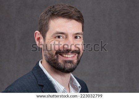 An adult male in his early forties with a full beard wearing a jacket and shirt.  He is laughing.