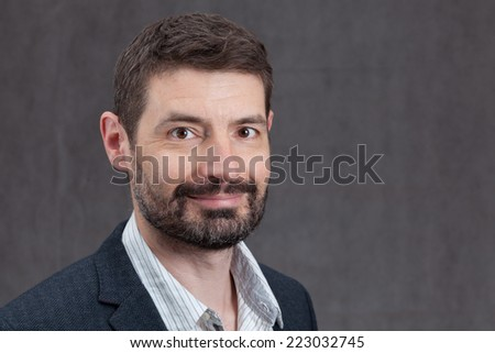 An adult male in his early forties with a full beard wearing a jacket and shirt.  He is smiling. - stock photo