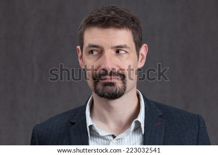 An adult male in his early forties with a goatee beard wearing a jacket and shirt.  He is smiling and looking to the left. - stock photo