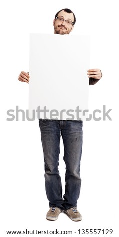 An adult man at his early 30's wearing casual sneakers, a pair of blue jeans and holding a large blank white sign. He's looking at the camera with a goofy expression. Isolated on white background. - stock photo