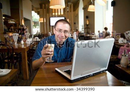 An adult man is sitting in a bar with a notebook on the table and coffee with cream in his hand