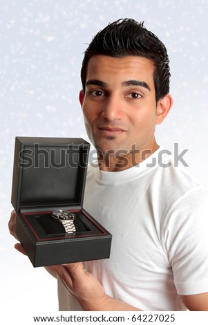 An adult man showing  or holding up a watch or other product in a box.