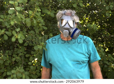 An adult man wearing a gas mask against a wooded background. - stock photo