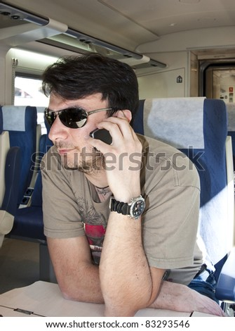 An Adult Man with Smartphone using Wireless Network on Train - stock photo