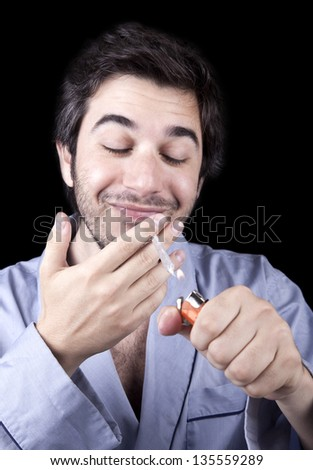 An adult man (30 years old), which  appears to be quite a bum, looking extremely delighted as he is about to start smoking a marijuana spliff (aka reefer; joint). Isolated on black background. - stock photo