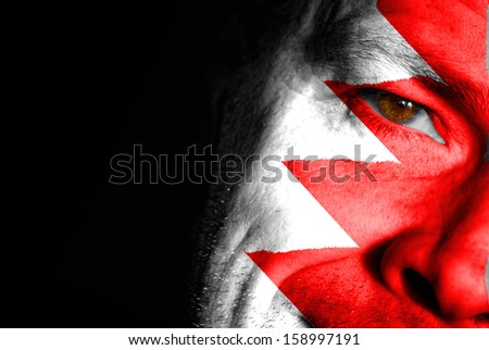 An adult sports fan with his face painted in the colors of Bahrain's flag - stock photo