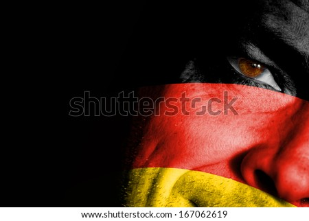An adult sports fan with his face painted in the colors of Germany's flag - stock photo