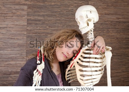 An adult woman leaning on a skeleton. - stock photo