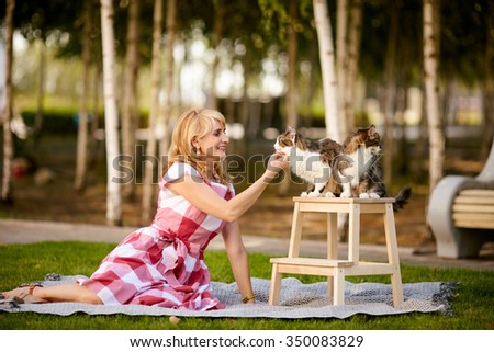 An adult woman playing with her cats in the park.