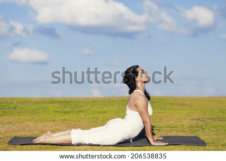 An adult woman standing on a black yoga mattress in the Urdhva Mukha Svanasana (aka upward facing dog) pose, on a green lawn with cloudy blue sky in the background. - stock photo