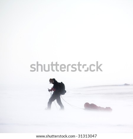 An adventurer in a cold winter storm - stock photo