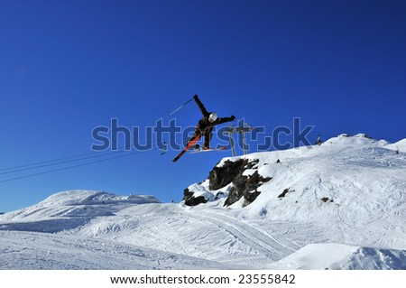 an aerial skier performs a full turn currently pointing backwards