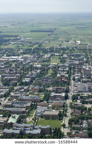 An aerial span of a university campus and the green plains behind it. - stock photo