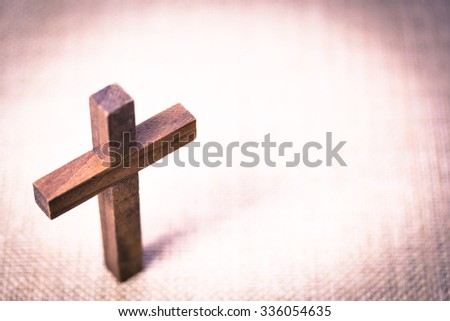 An aerial view of a holy wooden Christian cross on a burlap background. - stock photo
