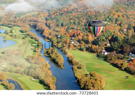 An aerial view of a hot air balloon floating over the Vermont country side
