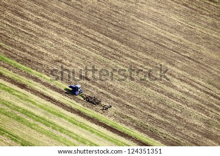 An aerial view of a tractor plowing a field - stock photo