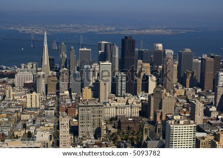 An aerial view of downtown San Francisco and Bay Bridge (Oakland port in the background) lit by a warm late afternoon sun. - stock photo