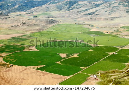 An aerial view of farmland and crop circles created by center pivot sprinkler systems - stock photo
