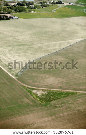 An aerial view of farmland irrigated with a center pivot irrigation system - stock photo