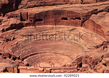An aerial view of the Roman-era amphitheater carved into the pink sandstone at Petra, Jordan. The building facades cut into the rock behind are ancient graves. - stock photo