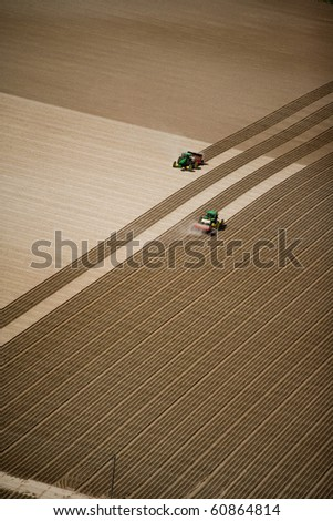 An aerial view of two tractors working in the fertile farm fields of Idaho, planting potatoes.  A great background image with a lot of area for text or copy. - stock photo