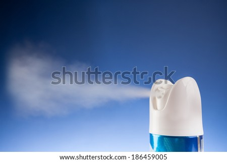 An aerosol can of spray dispensing its content - stock photo