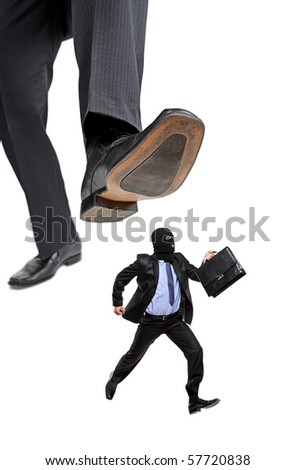 An affraid burglar running away from a big foot isolated on white background - stock photo