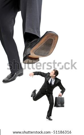 An affraid businessman running away from a big foot isolated on white background - stock photo