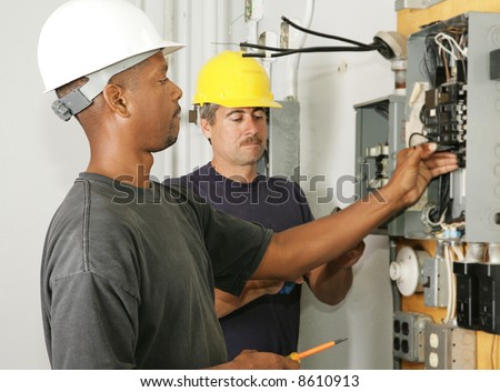 An african american and a caucasian electrician working on a panel.  Actual electricians performing work according to industry safety and code standards. - stock photo