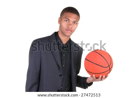 An African American basketball player holding a basketball while wearing his business casual suit - stock photo