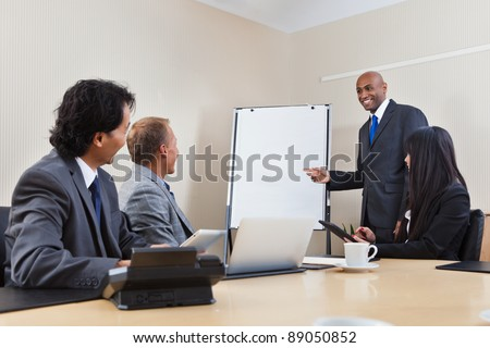 An African American business man giving a presentation to associates - stock photo