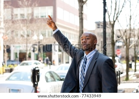 An African American business man raises his hand to hail a cab in the city. - stock photo