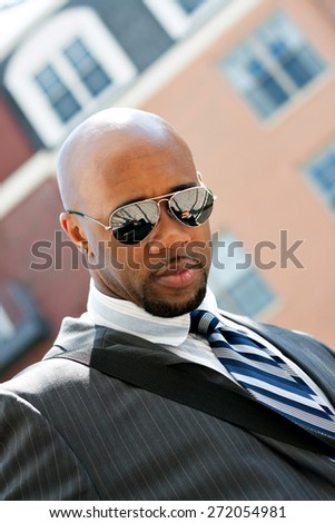 An African American business man wearing his sunglasses and business suit in the city with copy space. - stock photo