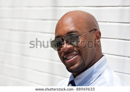 An African American business man wearing his sunglasses in the city. - stock photo