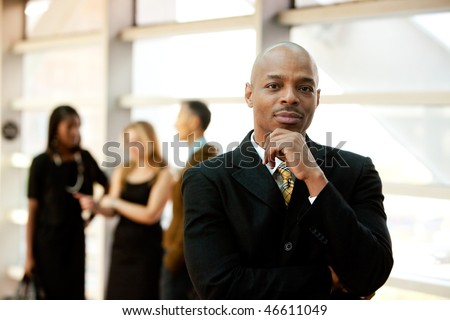 An African American business man with co-workers in the background - stock photo