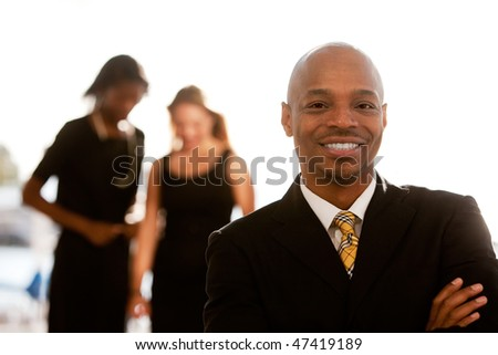An african american business man with colleagues in the background - stock photo