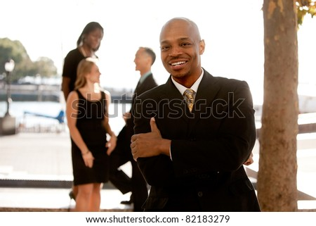 An african american business man with colleagues in the background