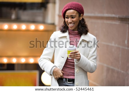 An African American business woman is walking through the city holding a cup of coffee tea or cappuccino. - stock photo