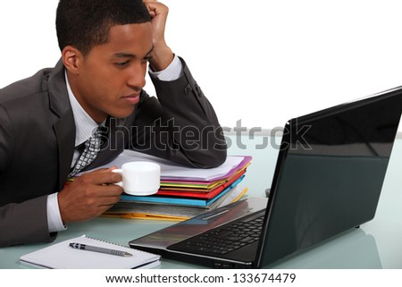 An African American businessman drinking a coffee while looking his laptop. - stock photo